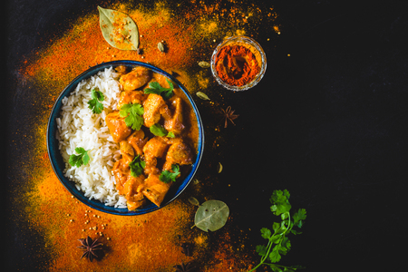 Photo pour Indian Butter chicken with basmati rice in bowl, spices, black background. Space for text. Butter chicken, traditional Indian dish. Top view. Chicken tikka masala. Indian cuisine concept. Overhead - image libre de droit