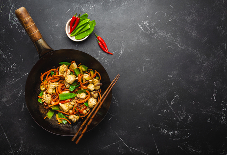 Photo for Stir fry chicken with vegetables in old rustic wok pan, chopsticks on black stone background, close up, top view. Traditional asian/thai meal, space for text - Royalty Free Image