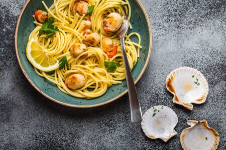 Photo pour Spaghetti with seafood, delicious fried cooked scallops served on blue plate, grey rustic concrete background, top view, close-up. Seafood pasta concept - image libre de droit