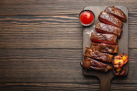 Photo for Grilled/fried and sliced marbled meat steak with fork, tomatoes, tomato sauce/ketchup on wooden cutting board, top view, close-up with space for text, rustic background. Beef meat steak concept - Royalty Free Image