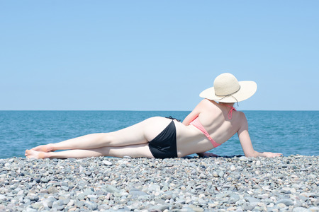 Not a tanned girl lies on the beach with a hat and sunbathes. Back view