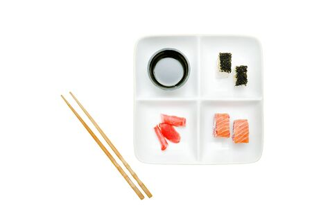 Square plate with rolls and sushi. Soy sauce, ginger and chopsticks. Food concept. Isolated. White background