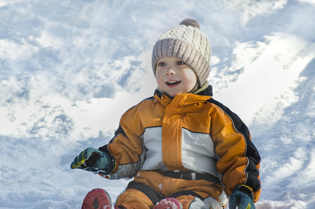 Foto per Boy in hat and orange jumpsuit slides off snow slide on back. Portrait. Close-up. Winter day - Immagine Royalty Free