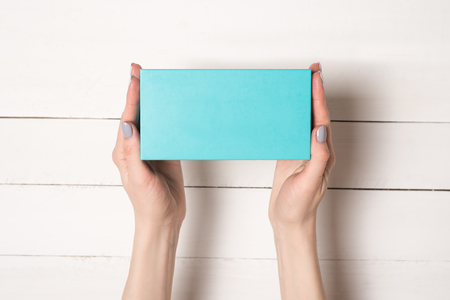 Photo for Rectangular turquoise box in female hands. Top view. White table on the background - Royalty Free Image