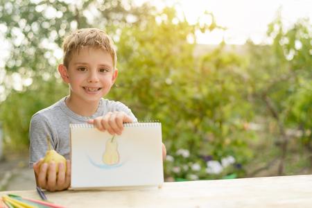 Foto de Cute boy shows drawn pear. Open air. Garden in the background. Creative concept. - Imagen libre de derechos