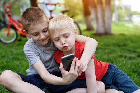 Photo pour Two boys using a smartphone are sitting on the grass. Bicycles in the background - image libre de droit