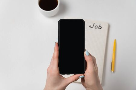 Female hand holding mobile phone. Notepad and cup of coffee. White background copy space.