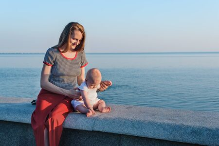 Photo for Young beautiful mother and little baby on promenade on sea background - Royalty Free Image