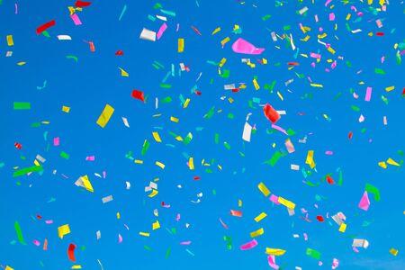 Foto de multicolored confetti on clear blue sky background - Imagen libre de derechos