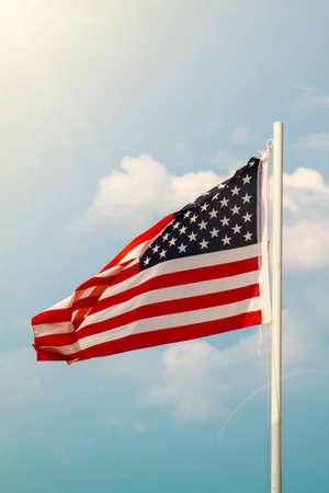 Photo pour American flag on a blue sky with clouds background - image libre de droit