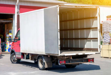 Photo pour small truck with red cab stands with open empty body ready for loading cargo. lipping path is included - image libre de droit