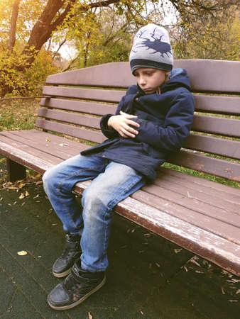 Photo pour sad boy sitting on bench alone outdoor - image libre de droit