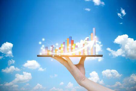 Photo pour Tablet on hand growth progress graph analysis or success business concept Sky background - image libre de droit