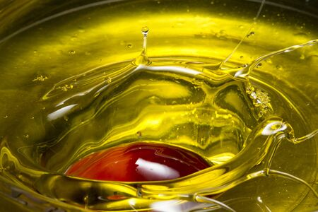 Photo pour Red Palm seed dropped in cooking palm oil with a splash in glass. Organic palm oil can be processed for food industry and produce energy as biodiesel and important agriculture economy in tropical Asia - image libre de droit