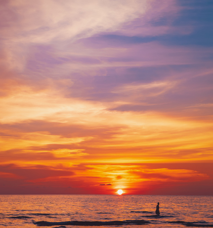 Photo pour Tropical colorful dramatic sunset with cloudy sky . Evening calm on the Gulf of Thailand. Bright afterglow. Silhouette of swimming man on the water - image libre de droit