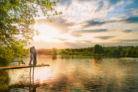 Photo pour Beautiful summer picture on the nature by the river. A loving couple is standing on the pier on a sunset background. - image libre de droit