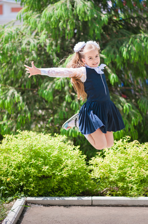 Photo pour A little girl in school uniform schoolgirl rejoices and jumps - image libre de droit