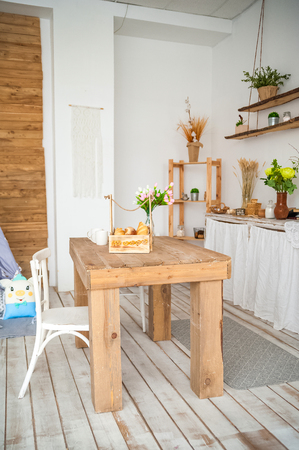 Photo pour Wooden table in a bright rustic-style kitchen. Scandinavian style in the kitchen. - image libre de droit