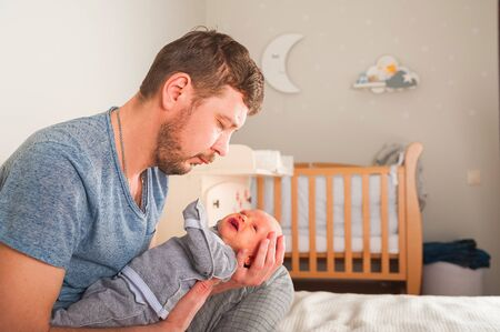 Father and newborn in Scandi bedroom interior. The father sings a lullaby to the child. Parent calms the baby before going to bed in his arms. Home care and baby care concept.