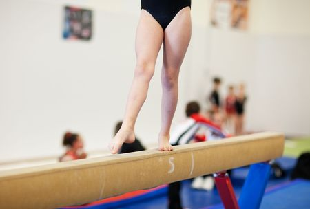 Photo pour A gymnastics competitor on the balance beam. - image libre de droit