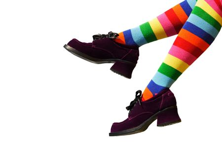 Striped knee-hi socks and wickedly wonky, purple suede shoes on isolated girl's legs.
