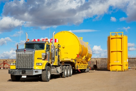 A yellow transport trailer picking up two newly manufactured and coated 400 BBL  oilfield storage tanks