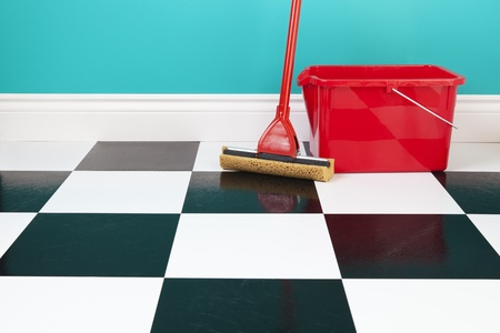 A red bucket and mop on a white and black checkered floor against a turquoise blue wall