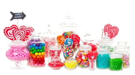 A candy buffet with a wide variety of candies in apothecary jars   Shot on white background