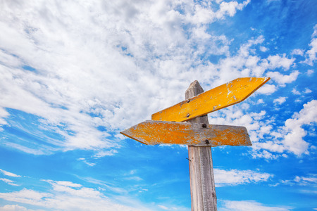 Photo pour Rustic yellow crossroads sign against a cloudy blue sky. - image libre de droit