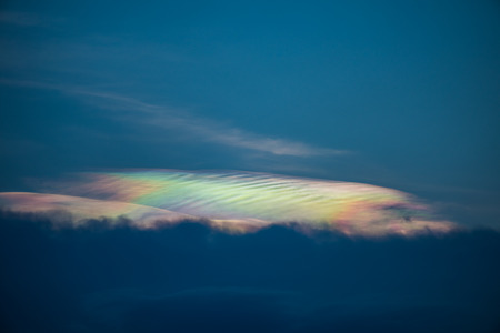 Photo pour Beautiful abstract iridescence cloud irisation or rainbow cloud shining out from behind the cloud on sunset time - image libre de droit