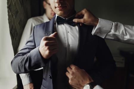 Foto de stylish groomsmen helping happy groom getting ready in the morning for wedding ceremony. luxury man in suit in room. space for text. wedding day. - Imagen libre de derechos