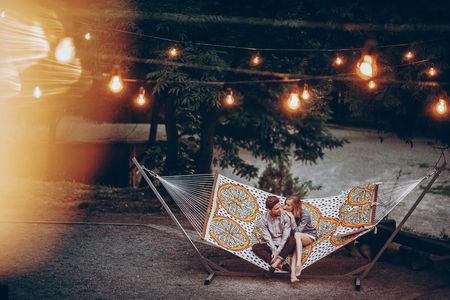 Romantic hipster couple enjoy rest on a hammock at park resort, cute woman lying with handsome man, lights in the backgroundの写真素材