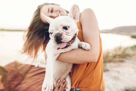 Foto de happy hipster woman playing with bulldog on the beach in sunset light, summer vacation. stylish girl with funny dog resting, hugging and having fun in sun, cute moments. space for text - Imagen libre de derechos