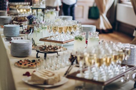 Foto de stylish champagne glasses and food appetizers on table at wedding reception. - Imagen libre de derechos