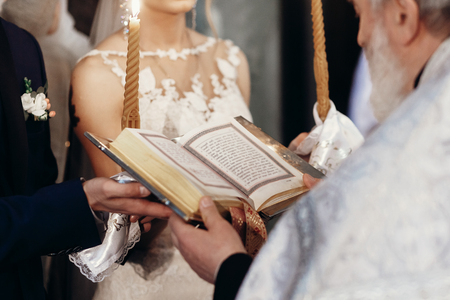 priest holding gospel. stylish bride and groom holding bible with priest at holy matrimony in church. spiritual love couple during wedding ceremony.
