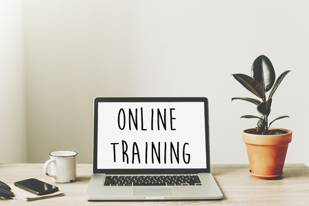 Photo for online training text on laptop screen on wooden desktop with phone, notebook, coffee and plant. business workspace. internet Education concept. e-learning - Royalty Free Image