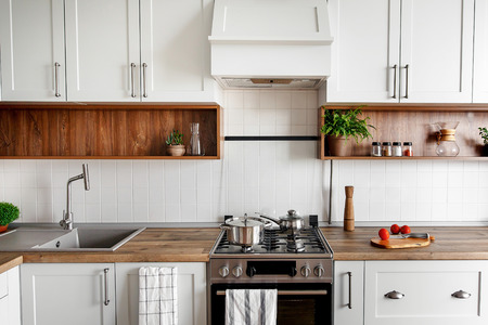 Foto de Stylish kitchen interior with modern cabinets and stainless steel appliances in new home. design in scandinavian style. cooking food. green plants decor, wooden worktop, sink and stove - Imagen libre de derechos