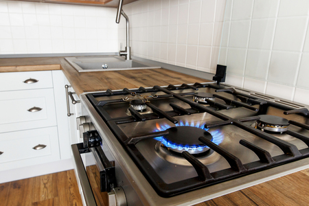 Photo pour burning gas from kitchen stove on background of stylish kitchen interior with modern cabinets and stainless steel appliances. flames from modern cooker. design in scandinavian style - image libre de droit