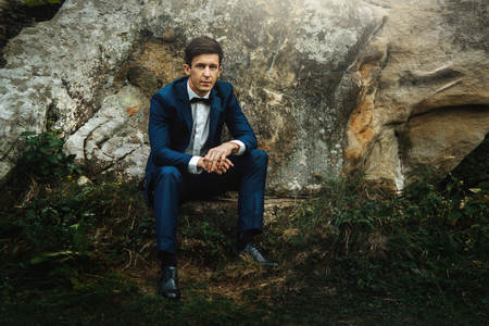 Photo for stylish elegant happy groom in fashionable suit posing on background of rocks in mountains - Royalty Free Image