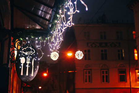 Stylish christmas decorations, garland lights on window of cafe or restaurant, food sign, in european city street. Festive decor and illumination in city center, winter holidays