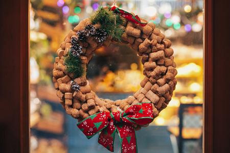Foto de Creative christmas wreath of wine corks, pine cones and red bow on door or window   in european city street. Stylish christmas street decor, Festive decorations and illumination. Winter holidays - Imagen libre de derechos
