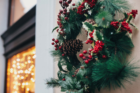 Photo pour Stylish christmas wreath with red berries,ornaments, pine cones, branches on building in european city street. Festive decorations and illumination in city center, winter holidays. - image libre de droit