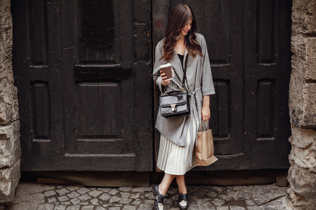Foto de Gorgeous young woman with cup of coffee and bag, smiling and standing at old wooden door in city street. Stylish happy hipster girl with beautiful hair and perfect smile shopping - Imagen libre de derechos