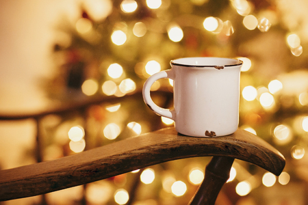 Photo pour cozy winter holidays. warm atmospheric moment . mug with hot drink on old wooden chair on background of golden beautiful christmas tree with lights in festive room. - image libre de droit