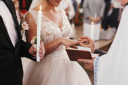 Foto de Priest putting on golden wedding ring on bride finger. Wedding matrimony in church. Exchanging wedding rings - Imagen libre de derechos