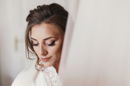 Foto de Gorgeous bride in silk robe holding stylish wedding dress in room in the morning. Happy sexy Bride and her beautiful wedding gown. Woman getting ready. Space for text - Imagen libre de derechos