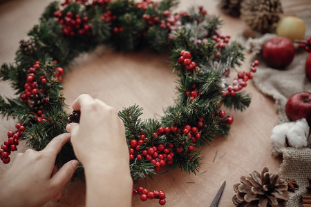 Photo pour Rustic Christmas wreath. Hands holding fir branches, red berries and pine cones,rope, scissors, cinnamon, cotton on rustic wooden background. Atmospheric moody image at holiday workshop - image libre de droit