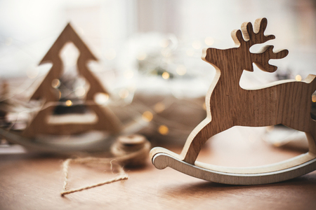 Photo pour Rustic reindeer christmas toy on wooden table on background of wooden tree,lights, twine, gift in linen fabric with green branch, pine cones. Simple eco presents. Zero waste holidays - image libre de droit