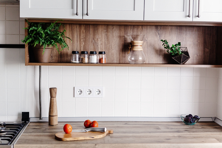 Photo pour Cooking food on modern kitchen with furniture in grey color and wooden tabletop.  Knife on wooden cutting board with vegetables, pepper, spices. Stylish kitchen interior  in scandinavian style - image libre de droit
