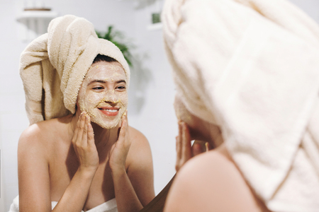 Photo pour Skin Care concept. Young happy woman in towel making facial massage with organic face scrub and looking at mirror in stylish bathroom. Girl applying scrub cream, peeling and cleaning skin - image libre de droit